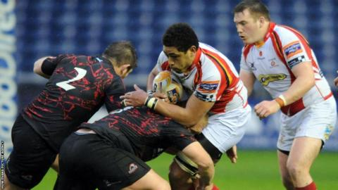 Number eight Toby Faletau is driven back by the Edinburgh defence as Newport Gwent Dragons end their season with a 31-24 defeat