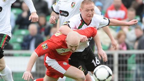 Cliftonville's Ryan Catney holds off Stephen McAlorum in a midfield tussle
