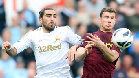 Swansea City defender Chico Flores tangles with Manchester City striker Edin Djeko during the 0-0 Premier League draw at the Liberty Stadium.
