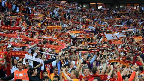 Galatasaray fans hold scarves as they support their team during the title winning match at the 52,652 capacity Turk Telekom Arena