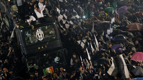 Juventus' players celebrate from the bus in the centre of Turin after winning the 'Scudetto'