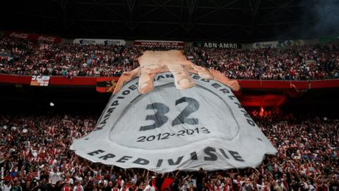 Ajax fans hold a massive banner in Amsterdam Arena showing a hand on their 32nd Dutch title during the Eredivisie match against Willem II Tilburg.