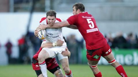 Ulster centre Darren Cave shrugs off the challenge of Scarlets lock Johan Snyman