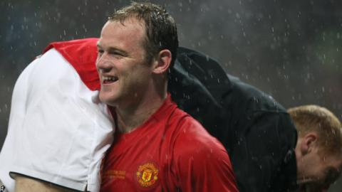 Manchester United's Wayne Rooney celebrates winning the Champions League trophy by carrying team mate Paul Scholes over his shoulder