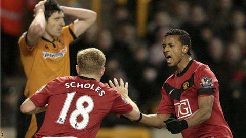 Manchester United's Paul Scholes (left) celebrates with his team mate Luis Nani after scoring the first goal of the game making it his 100th Premier League goal