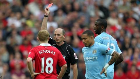 Manchester United's Paul Scholes (left) is shown a red card by referee Mike Dean after a challenge on Manchester City's Pablo Zabaleta