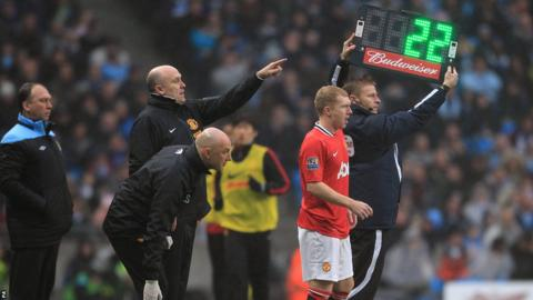 Manchester City Coach David Platt (left) looks on as Manchester United's Paul Scholes (right) prepares to go onto the pitch
