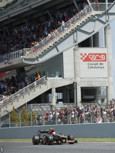 Romain Grosjean drives his Lotus in front of the packed grandstand