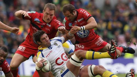 Nathan Hines of Clermont is tackled by Gethin Jenkins and Frederic Michalak of Toulon