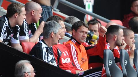 Michael Owen gives a thumbs-up signal from the Stoke bench