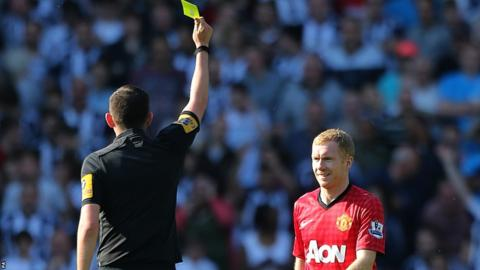Paul Scholes is shown a yellow card by referee Michael Oliver