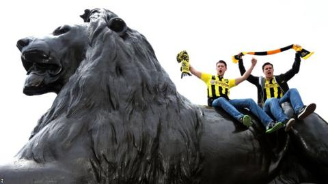 Borussia Dortmund fans on top of one of the lions in Trafalgar Square