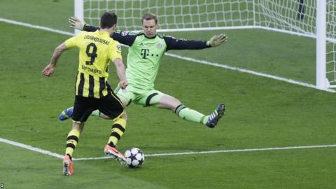 Bayern goalkeeper Manuel Neuer blocks a shot by Dortmund's Robert Lewandowski