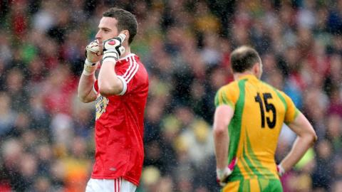 Goalkeeper Niall Morgan indicates that he can't hear any applause after scoring a free for Tyrone