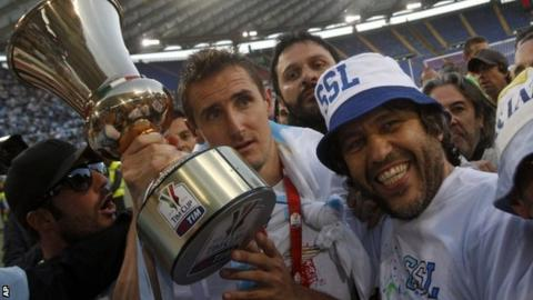 Lazio striker Miroslav Klose shows the Italian Cup to fans after his side's victory over Roma