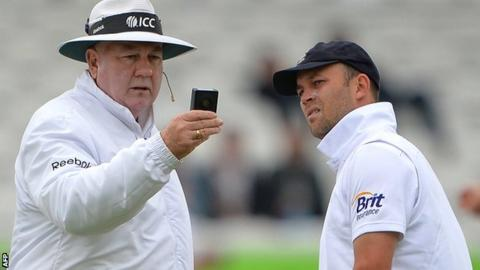 Umpire Steve Davis checks the light meter, watched by England's Jonathan Trott