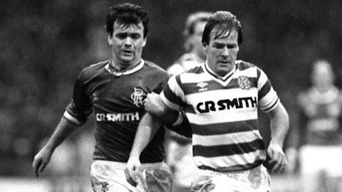 Celtic midfielder Murdo MacLeod is trailed by Rangers winger Davie Cooper