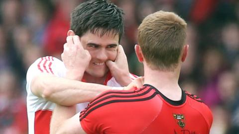 Derry defender Chrissy McKaigue and Mourne forward Benny Coulter get to grips with each other early in the game