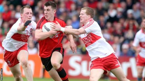 Down's Ryan Boyle in possession against Enda Lynn and Brian McCallion of Derry