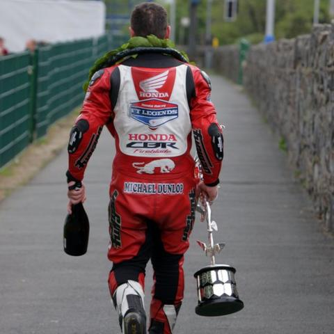 Michael Dunlop leaves the scene of his triumph with a bottle of bubbly and the coveted TT Superbike trophy