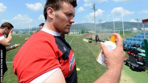 Wales' Emyr Phillips applies sun cream during training