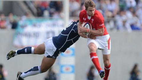 Liam Williams of Wales tries top elude the clutches of Japan centre Craig Wing during the build-up to Wales' try during the 22-18 win in Osaka