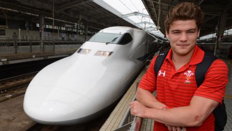 Wales wing Harry Robinson prepares to board the Bullet Train for the journey between Osaka and Tokyo after Wales 22-18 victory over Japan in the first Test match.