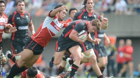 Harry Robinson of Wales is tackled by Hiroshi Yamashita of Japan