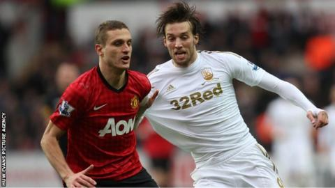 Manchester United's Nemanja Vidic competes with Swansea's Michu for the ball