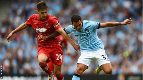 Southampton captain Adam Lallana (left) challenges Manchester City's Carlos Tevez