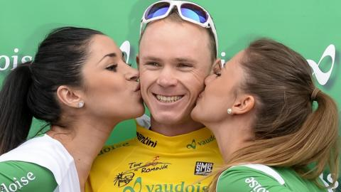 Chris Froome (centre) receives a traditional end-of-stage kiss from a couple of promotional girls