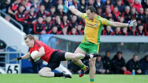 Brendan McArdle of Down hits the deck as Donegal forward Michael Murphy moves in at Breffni Park