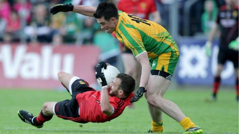 Conor Laverty of Down falls as David Walsh of Donegal attempts to win possession at Breffni Park