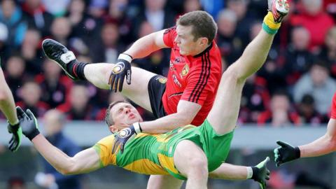 Donegal's Ryan Bradley is sent flying as Calum King of Down challenges for the ball at Breffni Park