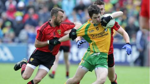 Conor Laverty and Ryan Boyle of Down combine to check an attack by Donegal's Ryan McHugh