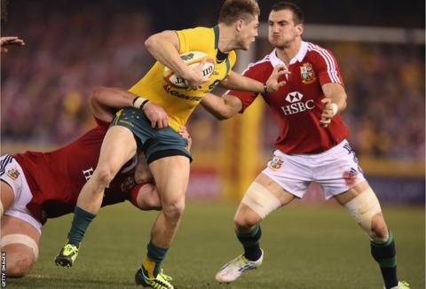 British and Irish Lions forwards Dan Lydiate and Sam Warburton team up to tackle Australia fly-half James O'Connor during the first half of the second Test in Melbourne.