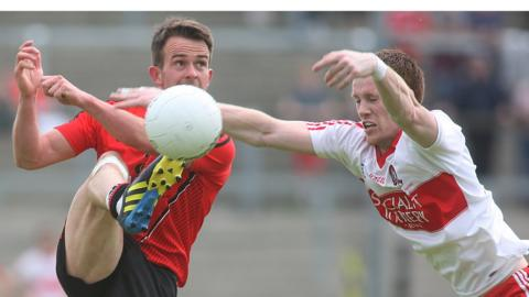 Mark Poland clears the ball as Aidan McAlynn closes in during Derry's second round qualifier win over Down