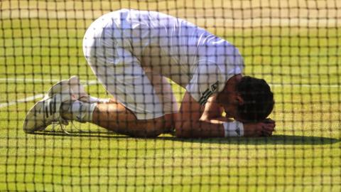 Andy Murray kneels on the turf after securing victory