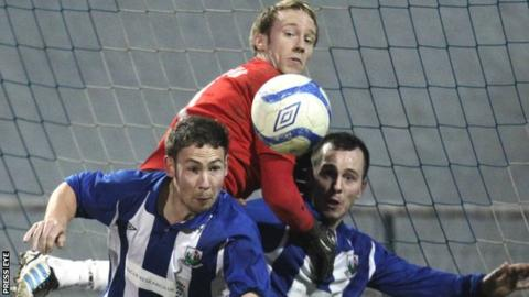 Billy Brennan climbs above two Newry City players