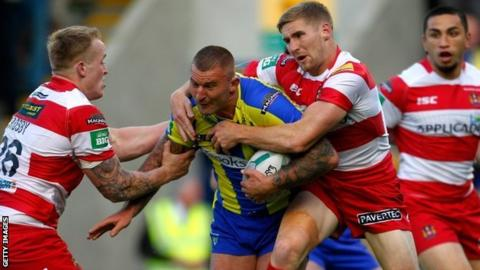Warrington's Paul Wood is tackled by Wigan's Sam Tomkins and Dom Crosby