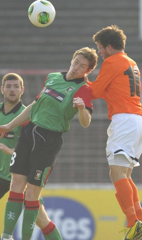 Glentoran midfielder David Howland contests a high ball with KR Reykjavik's Jonas Saevarsson at the sunny Oval