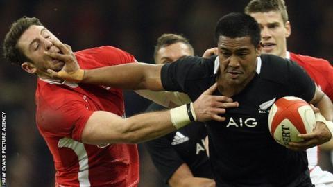 New Zealand's Julian Savea hands off Wales' Alex Cuthbert in 2012