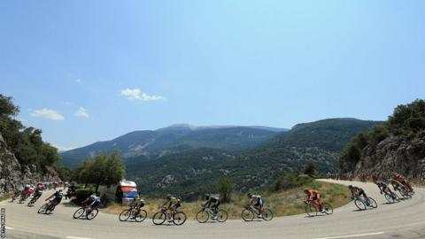 The peloton winds through the hills with Mont Ventoux in the background