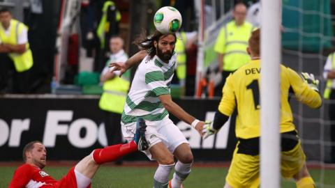 Celtic striker Georgios Samaras closes in on the Cliftonville goal as goalkeeper Conor Devlin prepares for action