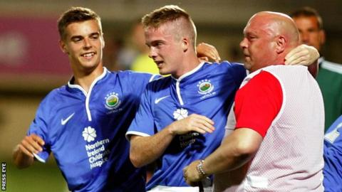 David Jeffrey embraces Linfield goalscorer Aaron Burns with Matthew Clarke also in the picture