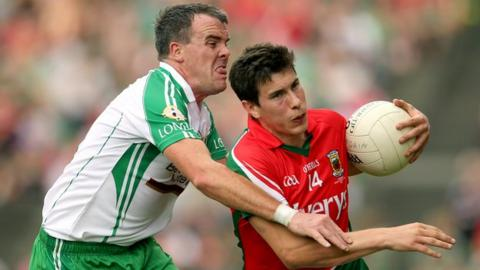 Alan Freeman and Shane Mulligan battle for possession