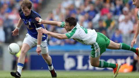 Martin Dunne of Cavan attempts to evade the diving challenge of London player David McGreevy at Croke Park