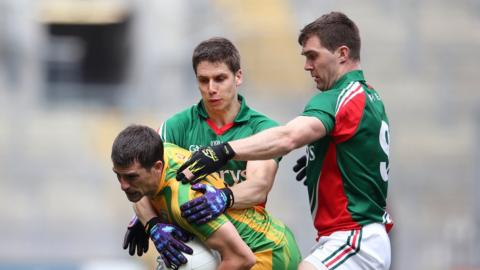 Mayo players Lee Keegan and Seamus O'Shea tackle Paddy McGrath