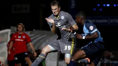 Leicester's Chris Wood (left) braces himself in the air against the clearance from Wycombe's Kortney Hause