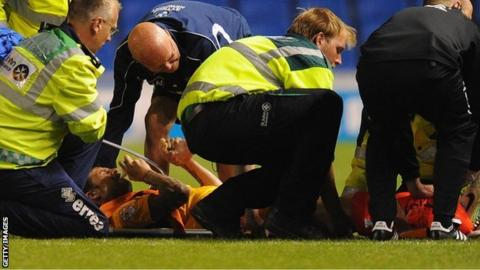 Byron Anthony receives treatment on the pitch at Brighton